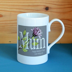 A white Mother's Day mug with a grey, pink and green flower pattern printed on it.