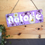 Personalised bedroom door sign in purple with a flower pattern design and a name in white lettering.
