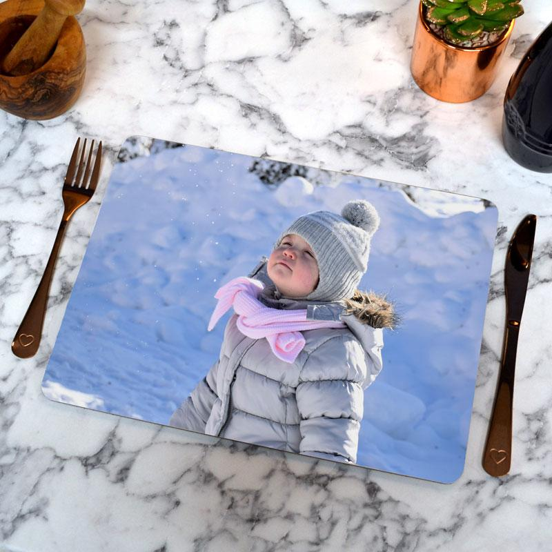 A personalised rectangle placemat with a photo of a child in the snow printed on it