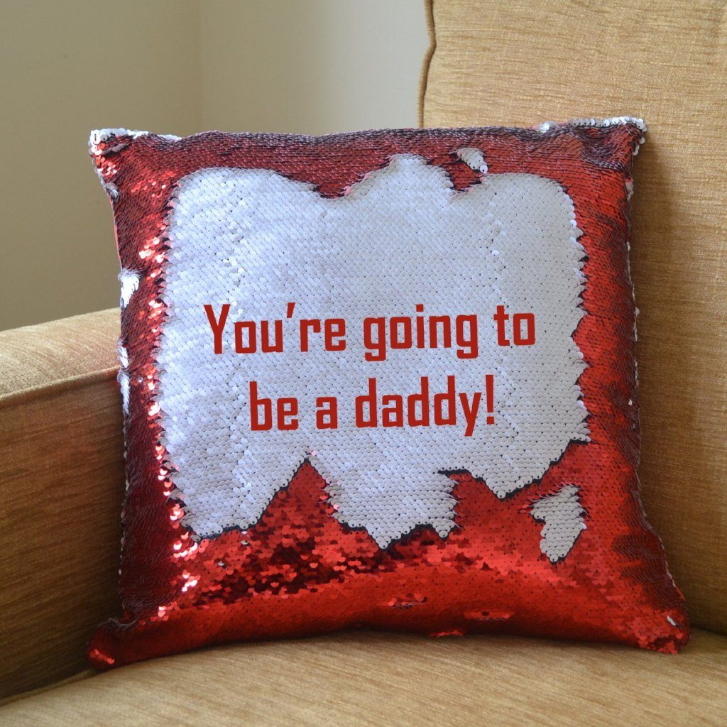 "A red reveal cushion showing the secret message ""You're going to be a daddy!"""