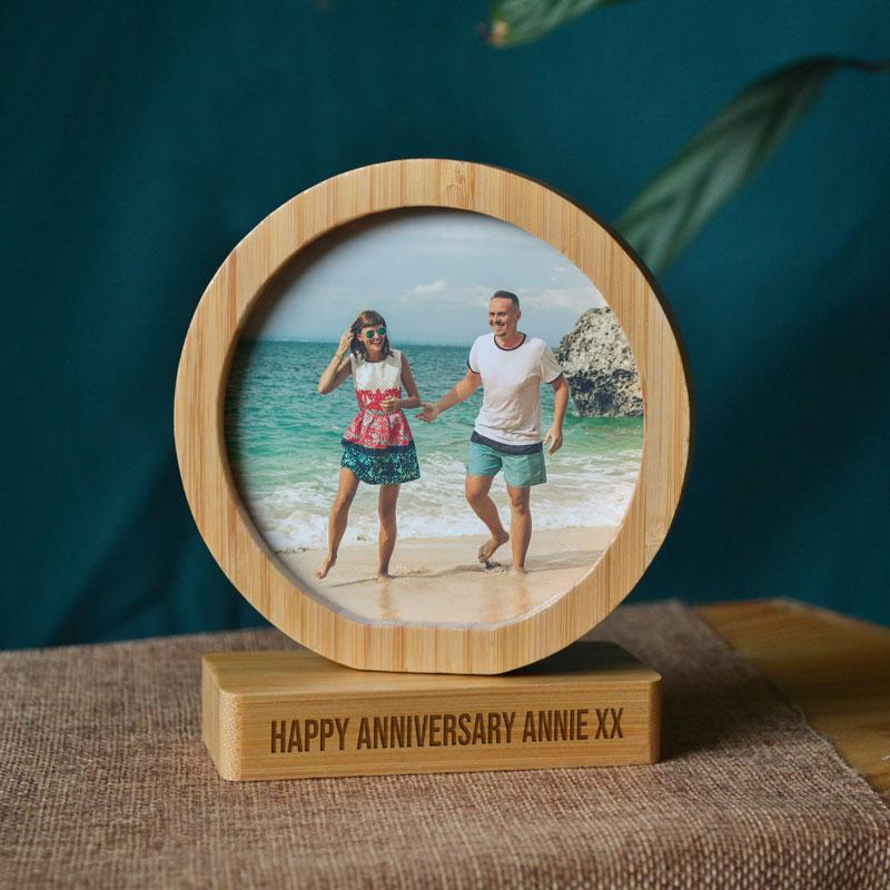 "A round bamboo photo frame with a photo of a couple on a beach printed in it. The base of the frame is engraved with the words ""Happy Anniversary Annie xx"""