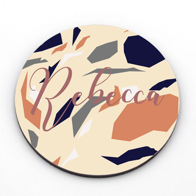 A personalised round coaster printed with a terrazzo pattern and customised with a name in script lettering