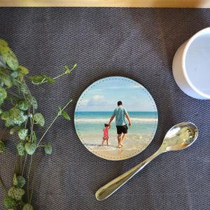 A personalised round coaster in PU leather with a holiday photo printed on it