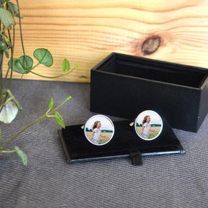 Personalised round photo cuff links in a black box. The cuff links have a photo of a little girl printed on them.