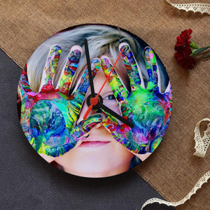 A personalised round clock with a close up photo a child with paint on her hands