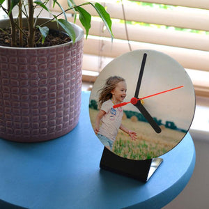 A personalised table top clock on a small stand. The clock has a family photo printed on it.