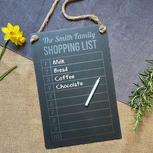 "A personalised rectangular slate notice board with the words ""the Smith family shopping list"" engraved at the top."
