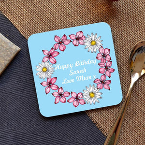 A personalised birthday coaster featuring flowers and a message in white lettering