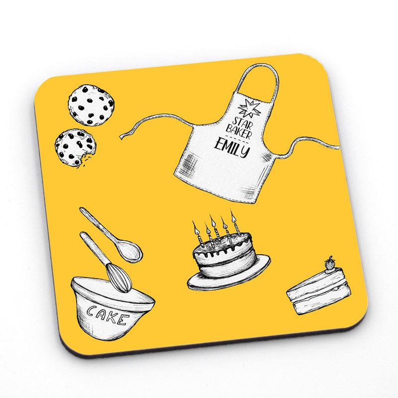 A yellow coaster with baking icons printed on it, the coaster is also personalised with a custom name.