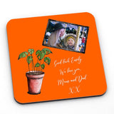 A personalised orange coaster with a house plant illustration, a family photo and a personal message in white lettering.
