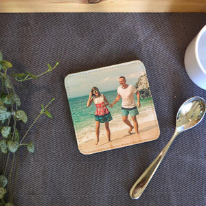 A personalised square PU leather coaster with a holiday photo printed on it.