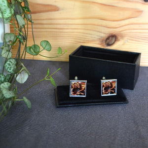 A pair of personalised square cuff links with photos of a man and a woman on holiday printed on them
