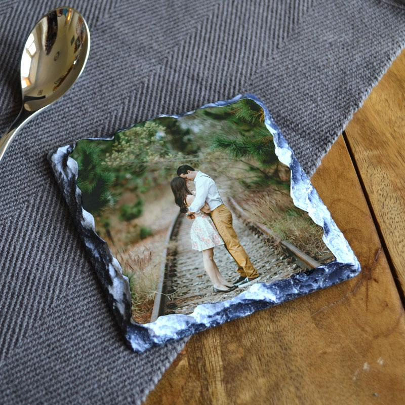 A personalised square slate coaster with a photo of a couple printed on it