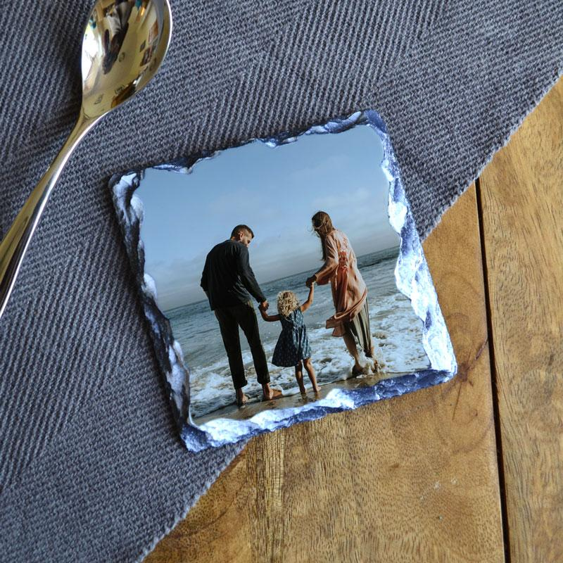 A personalised slate coaster with a family photo printed on the surface