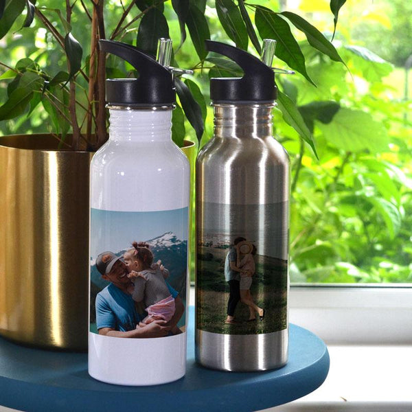 Two personalised photo water bottles with black lids, one in sliver and one in white, both have family photos printed on them.