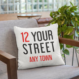 A personalised cushion with a street name and house number printed in large red and black lettering