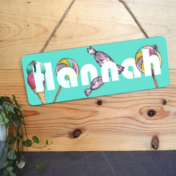 A personalised mint green sign with a sweet treats pattern and a name in white lettering