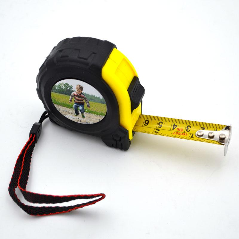 A personalised photo tape measure with a photo of a little boy printed on it