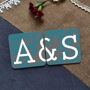 "a pair of personalised coasters in teal and grey. They are personalised with a couple's initials and when placed together the full message is visible. The message reads ""A&S"""