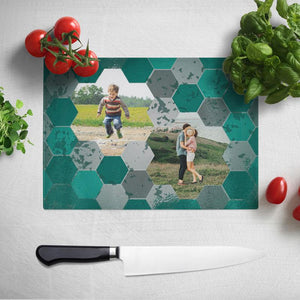 A rectangular glass chopping board with a geometric teal and grey pattern around two personal photographs