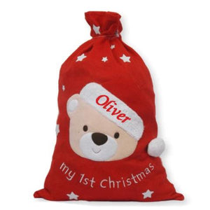 "A personalised red felt Christmas stack with a teddy bear featured on the front. The sack has an embroidered message reading ""my 1st Christmas"". The socking is personalised with the name ""Oliver"""