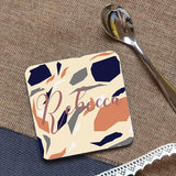 "A personalised terrazzo coaster, the coaster is square and has the name ""Rebecca"" printed onto it."
