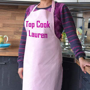 A personalised apron in light pink with hot pink printed lettering