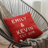 A personalised red cushion with red lettering printed on it