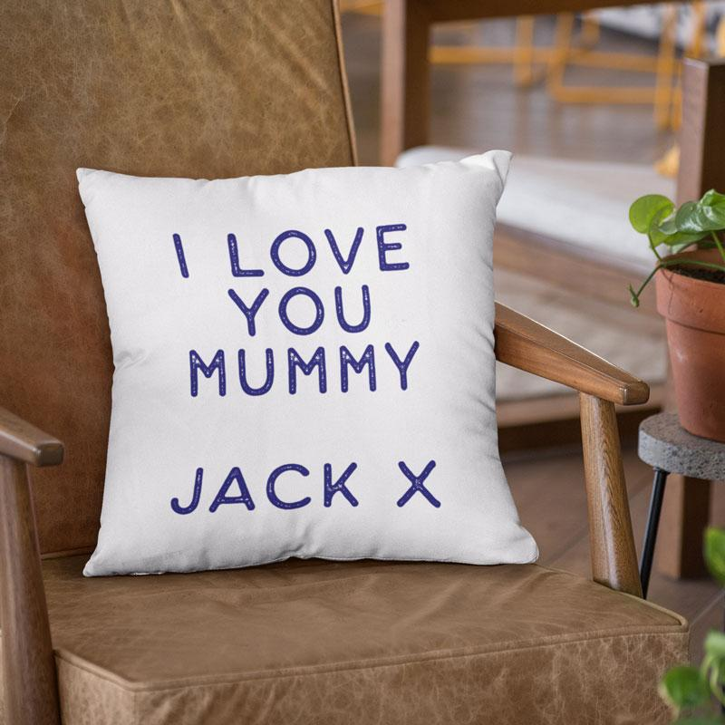 A personalised white cushion with navy blue lettering on it