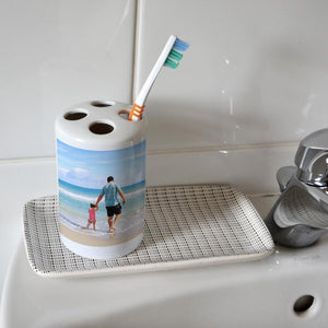 A personalised white photo toothbrush holder with a photo of a dad and daughter printed on it. The toothbrush holder is on the edge of a sink in a bathroom.