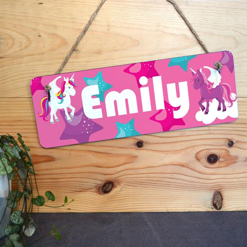 A personalised pink girl's bedroom sign with unicorns and stars.