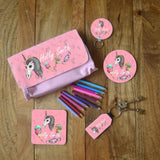 An image of a range of personalised unicorn products, the photo shows a pencil case, 2 coasters, a keyring and a name tag all with the unicorn design on.