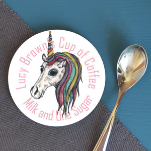 "A personalised round unicorn coaster. The design includes an ilustration of a unicorn and the message ""Lucy Brown's cup of coffee, milk and one sugar"""