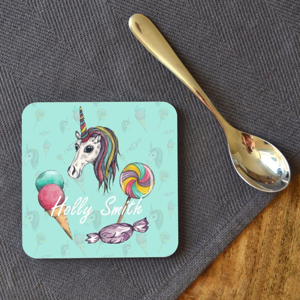 A personalised mint green unicorn coaster on a table with a tea spoon