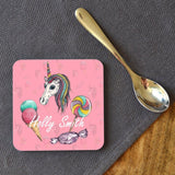 A photo of the personalised unicorn coaster on a table next to a tea spoon