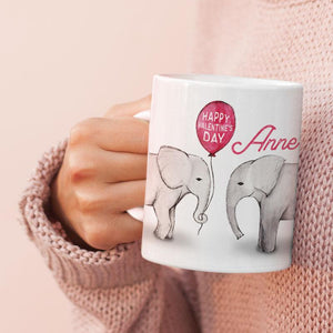 A woman holding a personalised mug with 2 elephants on
