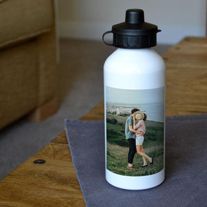 A personalised white metal water bottle with a photo printed on it.