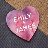 "A personalised heart shaped coaster with a pink and purple pattern and the words ""Emily + James"" in white lettering."