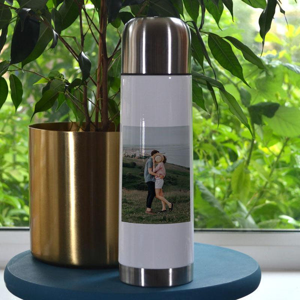 A personalised white travel flask with an image of a couple printed on it