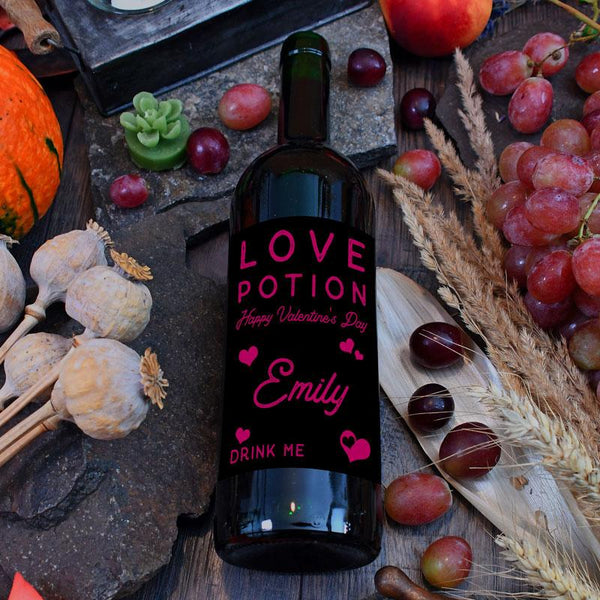 "A personalised wine bottle label with the words ""love potion"" included in the design. The lettering is in hot pink on a black background."