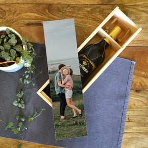 A personalised wooden wine box with a photo printed on the lid. Inside is a bottle of wine and the box has a rope handle.