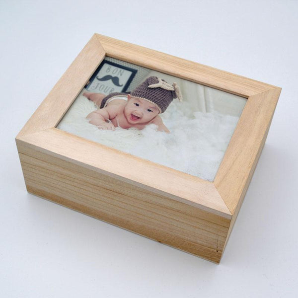 A personalised wooden memory box with a photo of a baby printed on the lid