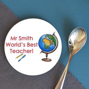 "a round personalised coaster which has a design including an illustration of a globe and a message which reads ""Mr Smith Worlds Best Teacher"""