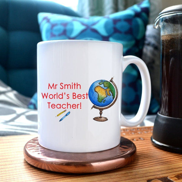 "A mug on a table next to a coffee pot. The mug has a personalised design which includes an illustration of a globe and a message which reads ""Mr Smith, world's best teacher"""