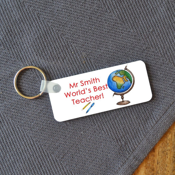 "A rectangular key ring on a table which has a personalised design on it. The design includes an illustration of a globe and the message ""Mr Smith, worlds best teacher"""