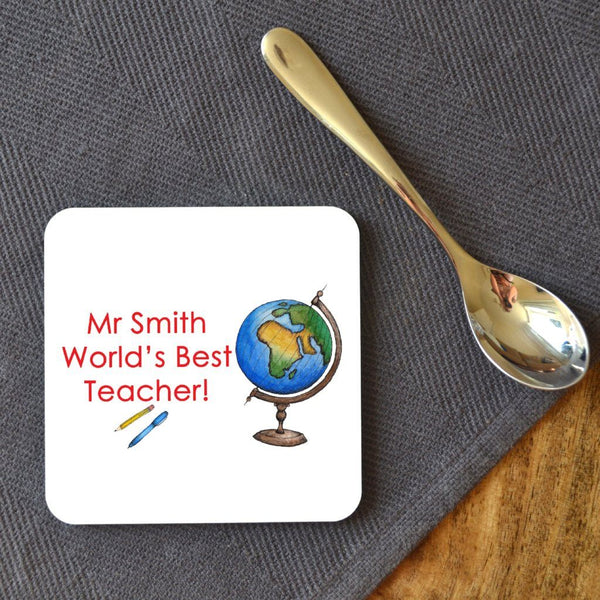 "A personalised square coaster on a table next to a tea spoon. The design includes an illustration of a globe and the message ""Mr Smith, world's best teacher"""
