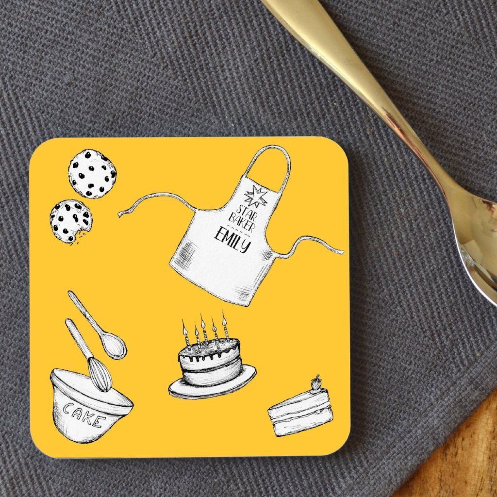 "A personalised square coaster with a yellow background and black and white illustrations of a birthday cake, 2 cookies, a mixing bowl and an apron which says ""Star Baker Emily"""