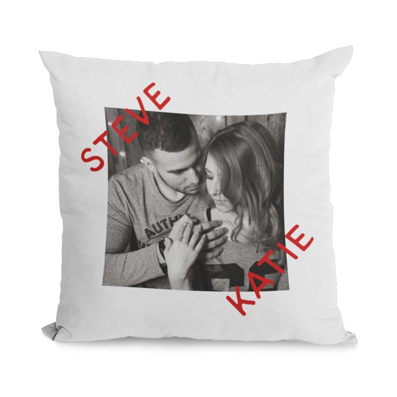 A personalised white cushion with a black and white photo of a couple and their names in red lettering