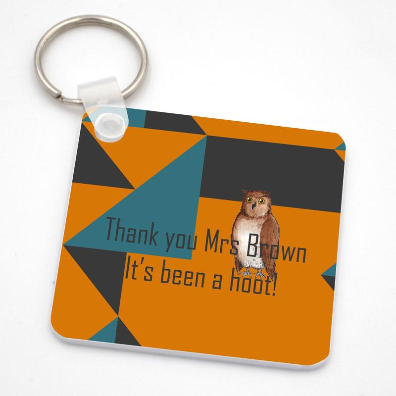 "A personalised square keyring in orange, grey and blue with an owl illustration. The keyring is printed with the words ""It's Been a Hoot"""