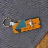"A personalised rectangle key ring. The design which includes an orange, teal and grey background, an illustration of an owl and a message which reads ""thank you Mrs Brown, its been a hoot!"""
